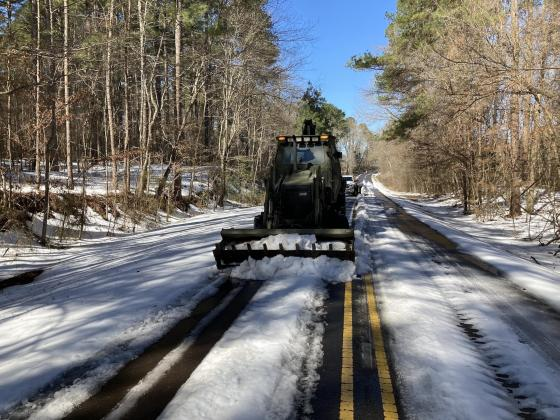 National Guard personnel clear an ice-covered road intersecting Firetower Rd. near Rocky Mount Monday.